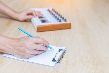 amateur musician, song writer hands writing a song on white paper on wooden desk