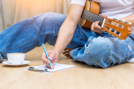 amateur songwriter playing acoustic guitar and writing a song on wooden floor