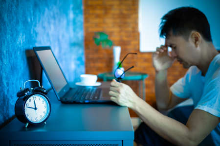 headache, tense young asian man working on laptop computer in bedroom at night Standard-Bild