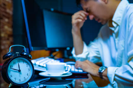 headache, tense young asian businessman working on computer at night