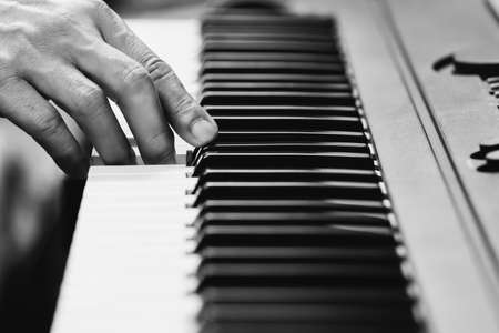 black and white male musician hand playing on piano keys. music concept Standard-Bild