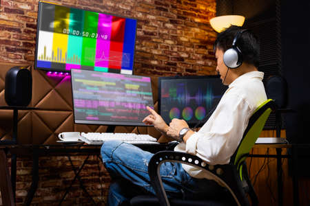 asian male media content creator editing video footage on computer in home studio. post production, broadcasting concept