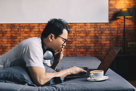 yawning asian man working on laptop computer in bedroom at night