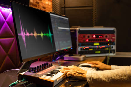 male music producer hands arranging a song on midi keyboard, computer and professional equipment in home recording studio Standard-Bild