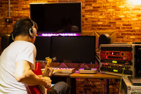 back of male musician enjoy playing electric guitar in home recording studio Standard-Bild