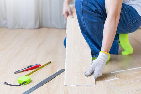 male worker hands replacing laminated wooden floor. home renovation, decoration concept Standard-Bild