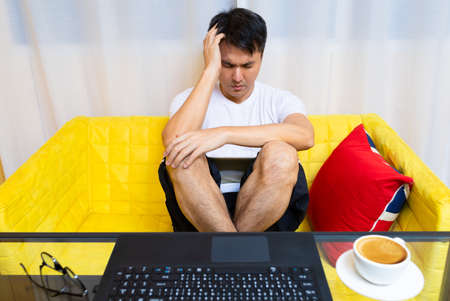 headache, tense young asian man working on laptop computer in living room at night Standard-Bild