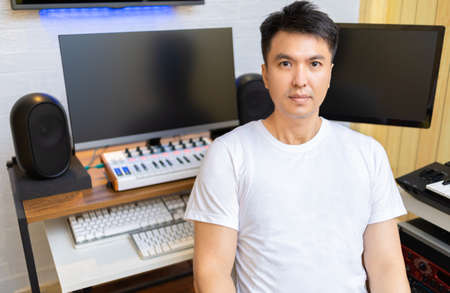 asian smart, healthy music composer smiling in home studio
