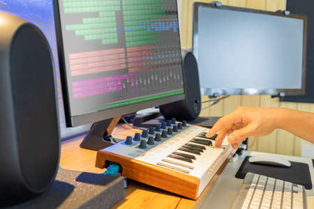 male songwriter hand playing keyboard for recording midi track on computer. music production concept