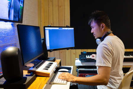 asian professional producer composing, editing music score on movie footage. recording, post production concept
