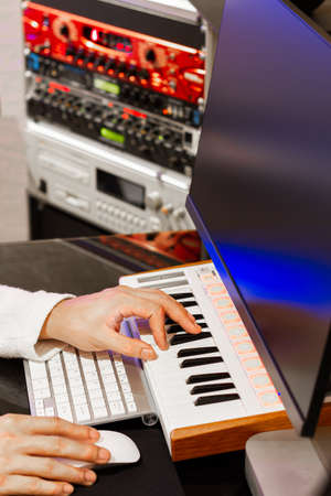 close up male music composer hands playing midi keyboard for recording on computer in sound studio Standard-Bild