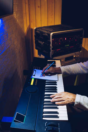 male songwriter playing electric piano and writing a song in home studio at night