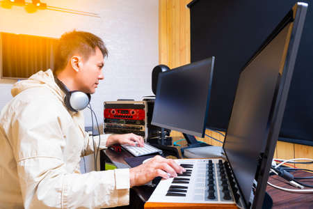 asian male music producer arranging a hit song on midi keyboard and computer. music production concept