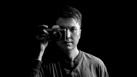 black and white asian man holding retro camera, isolated on black