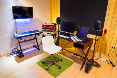 home recording studio showing professional audio equipment in small modern working space, wooden wall and floor