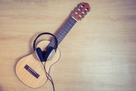 acoustic guitar and headphone on floor. music background