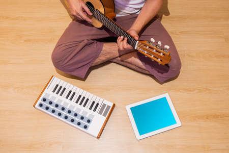 top view of amateur music composer, songwriter playing acoustic guitar and recording a song with midi keyboard and tablet computer on wooden floor