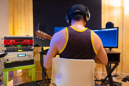 back of asian professional musician, producer recording acoustic guitar on computer in sound studio. music production concept Standard-Bild