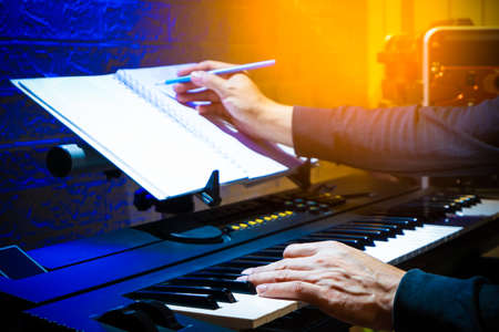 male musician, composer playing piano and writing a hit song in home studio. song writing concept