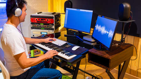 asian male producer arranging a song on midi keyboard and computer in home studio. music production, recording, post production technology concept