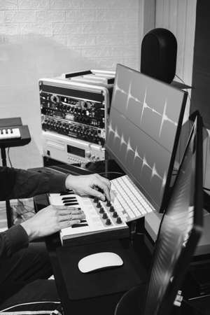 black and white male music producer hands tweaking midi keyboard knob for editing waveform on computer monitor in home studio Standard-Bild