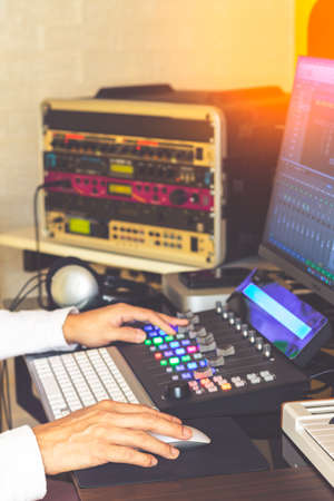 Sound engineer hands adjusting volume on digital audio control surface for mixing audio tracks on computer. Post production, broadcasting, recording concept