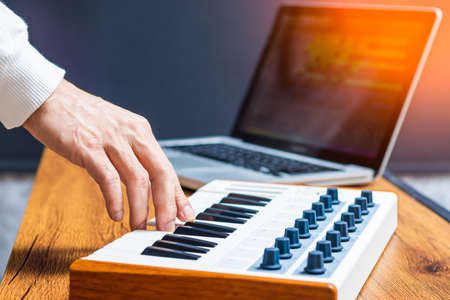 male producer, musician hand playing midi keyboard for arranging a song on laptop computer in home studio Stock fotó