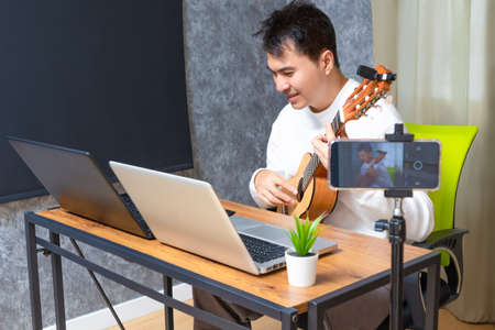 asian male happy music teacher streaming live acoustic guitar lesson to his students online. e-learning in modern technology concept 免版税图像