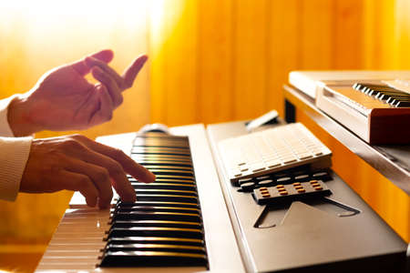 silhouette of composer hands playing on electric piano keys in home studio. close up. music background