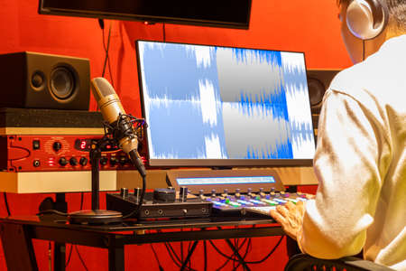 professional sound engineer recording, editing, mixing voice over waveform on computer in post production studio Stock fotó
