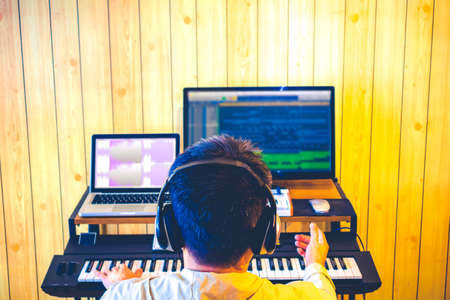 back of asian male music producer arranging a song on computer in home studio 免版税图像