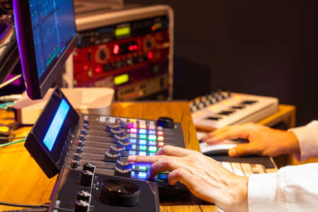 professional producer hands adjusting control surface fader for mixing audio and video on computer in post production and broadcasting studio 免版税图像