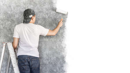 back of young asian man on ladder painting interior cement wall with paint roller for home renovation background 免版税图像