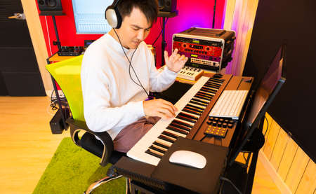 happy smiling asian handsome musician practicing electric piano lesson online from internet in home studio