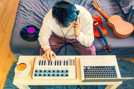 top view of asian man playing keyboard for learning music lesson online from internet