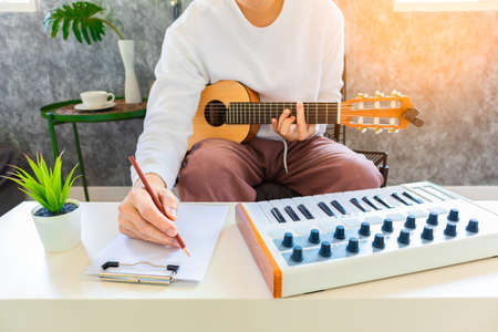 male amateur songwriter playing acoustic guitar and writing a song on white paper in living room 免版税图像