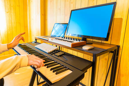 man hands playing on digital piano keys while learning music lesson from internet. music e-learning concept