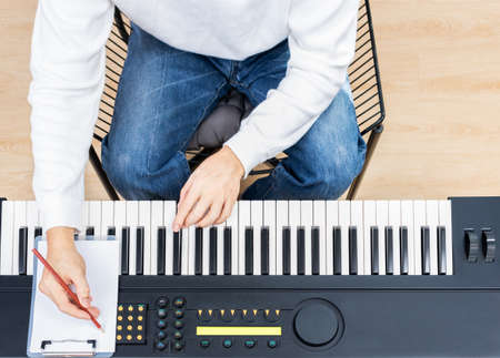 top view of male amateur songwriter playing electric piano and writing a song on white paper