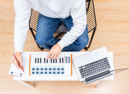 top view of male songwriter playing midi keyboard for recording on laptop computer and writing a song on white paper in living room 免版税图像