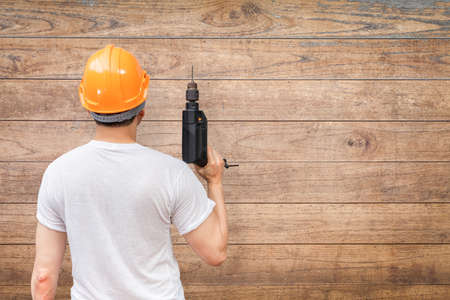 back of asian handyman holding electric drill on wooden wall background. home renovation concept