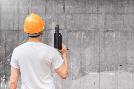 back of asian handyman holding electric drill on concrete wall background. home renovation concept