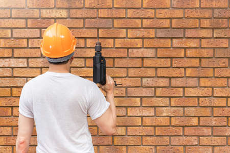 back of asian handyman holding electric drill on brick wall background. home renovation concept 免版税图像