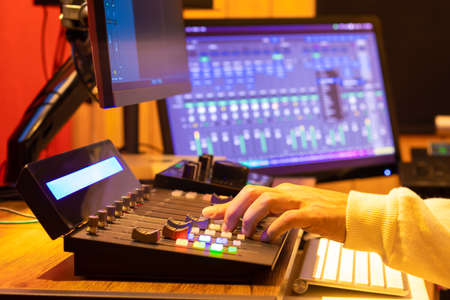 male technician, sound engineer hands editing and mixing audio on control surface panel in broadcasting, post production studio.