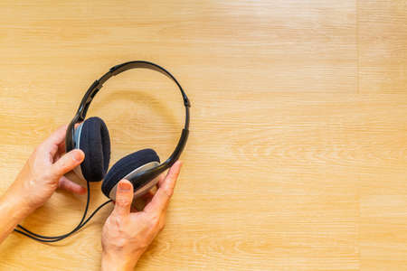 hands holding headphone on wooden background