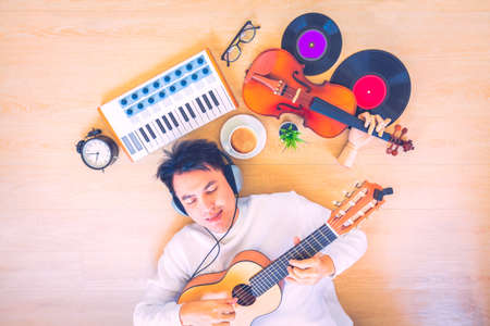 asian handsome male music lover lying on wooden floor and enjoy listening music while playing acoustic guitar with keyboard, violin, coffee cup, clock, glasses, record on floor