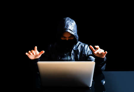 anonymous hacker with laptop in the dark. technological crime concept Stock fotó