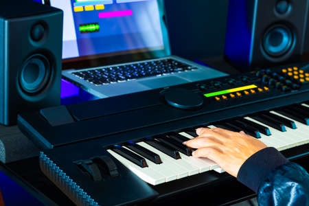 professional musician, producer hand playing on midi keyboard for recording music instrument track on laptop computer. music production concept