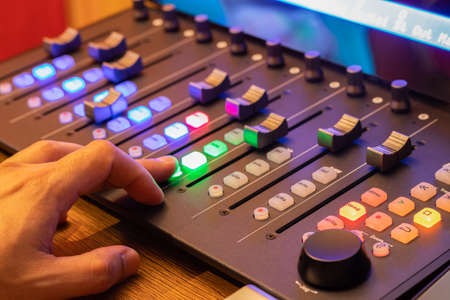 sound engineer, technician fingers pressing on control surface button for broadcasting, recording concept