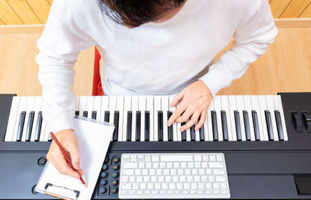 top view of young asian male songwriter writing a hit song while playing electric piano. songwriting concept