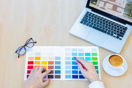 male designer using graphics tablet to choosing color swatch samples chart for selection coloring with laptop computer at workplace